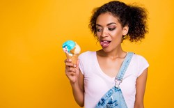 Woman gesturing tongue out looking at ice cream in waffle cone isolated on yellow background