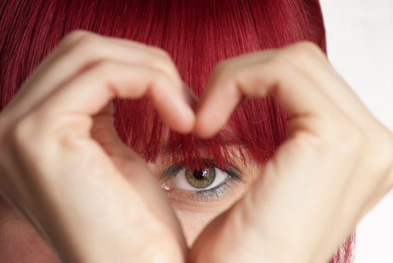 Woman framing her eye with heart hands
