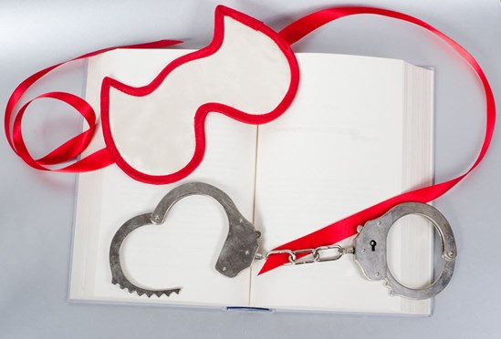 A book with blindfold and handcuffs