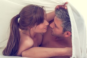 A naked couple kissing under the sheets
