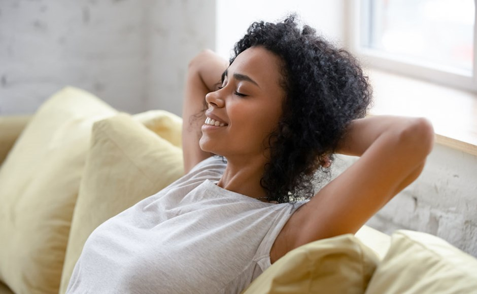 African American woman relaxing on comfortable couch