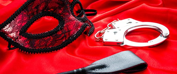 BDSM concept image with a mask, hand cuffs and a flogger