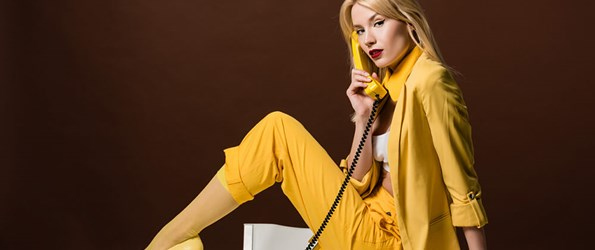 beautiful stylish blonde girl talking by yellow vintage phone