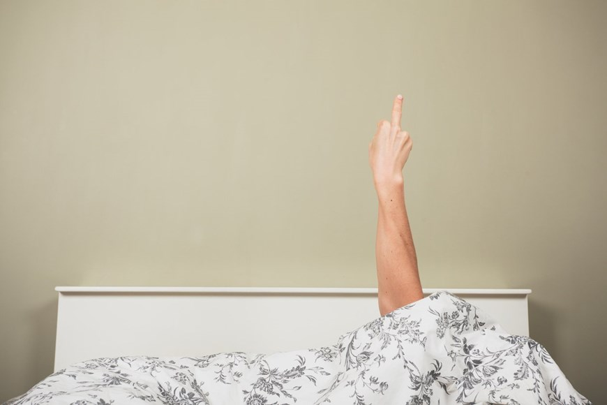 woman giving finger in bed