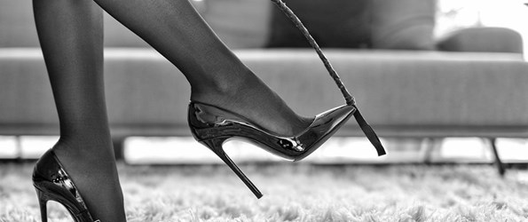 Black and white photo of person in high heels with black whip
