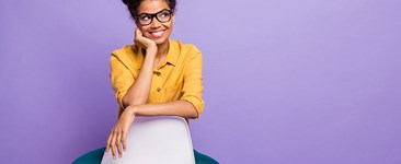Black woman sitting backwards on chair looking sideways