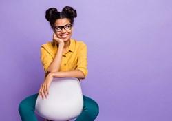 Black woman sitting backwards on chair looking sideways