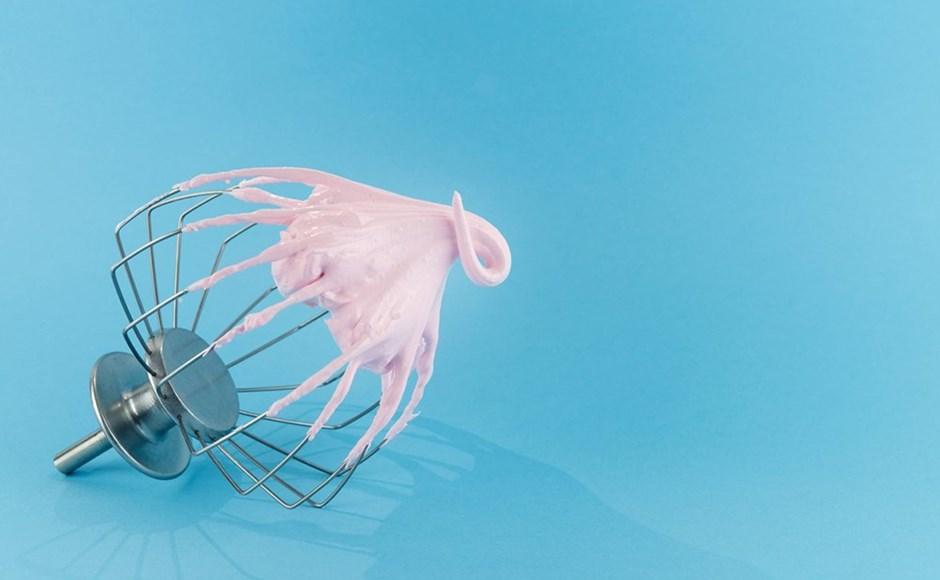 Blender rod with pink meringue on a blue background