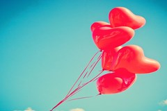 Cluster of heart shaped balloons in the sky
