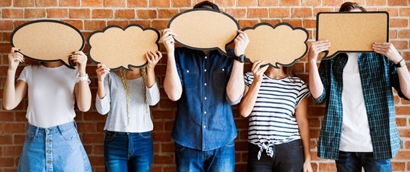 consent: a group of people hold up cardboard cut outs in the shape of thought bubbles and speech bubbles