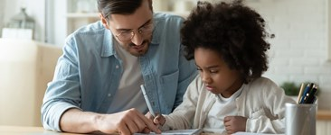 Dad helping daughter with homework at home