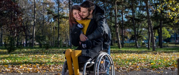 Disabled young woman with boyfriend enjoying beautiful autumn day in the park