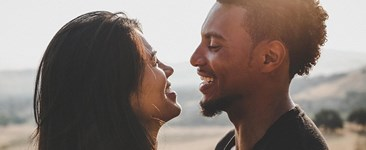 Diverse couple smiling at each other in the sun