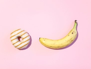 Donut and a banana on pink background