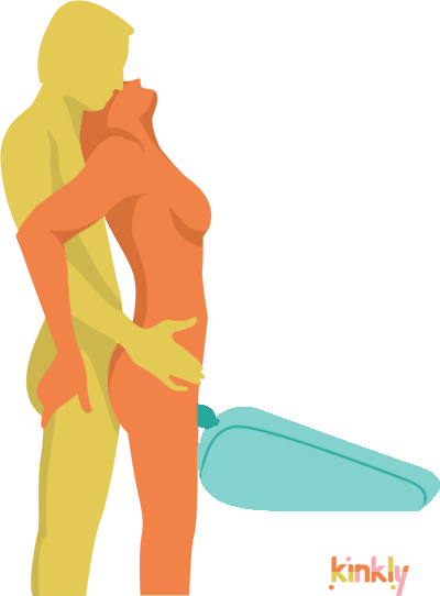 Twin Standing Pleasure Wand Massager Sex Position. A person with a clitoris is standing upright with their clit positioned on top of a wand massager that is being held by a sex shape called the Liberator Axis. The partner of the clitoris owner then comes up from behind to penetrate them.