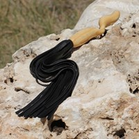 NobEssence Incite - A leather flogger with a carved wooden handle.