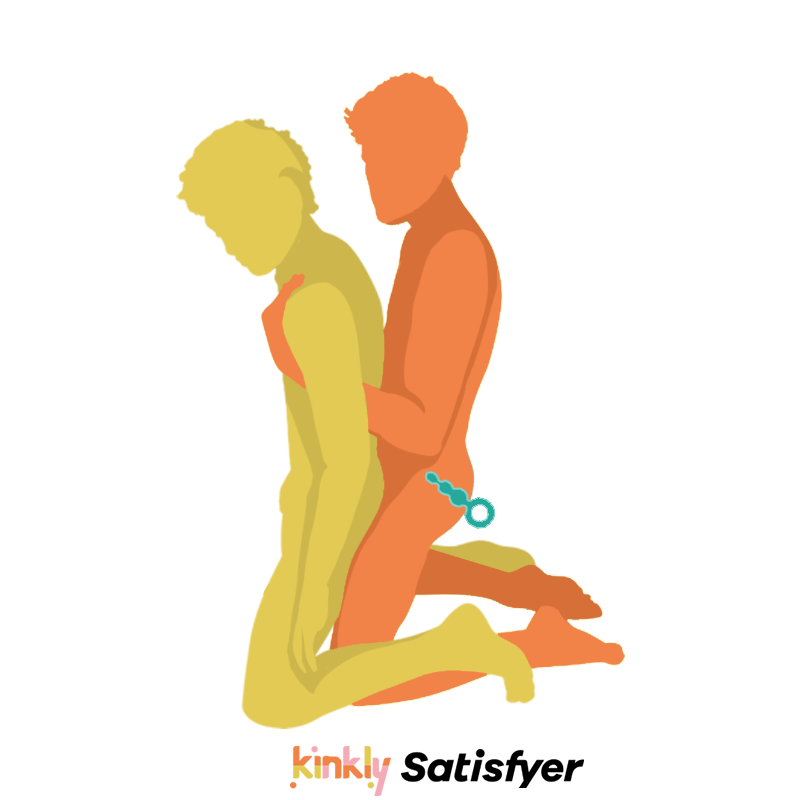 Double Hooked In Position with Satisfyer Plug. Couple is kneeling, facing in the same direction, one penetrating the other from behind. The penetrating partner is wearing an anal plug.
