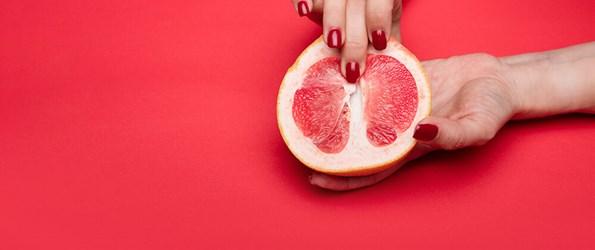 female hands pressing on half a grapefruit masturbation concept
