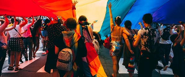 Group of people walking underneath a lgbtqia pride flag