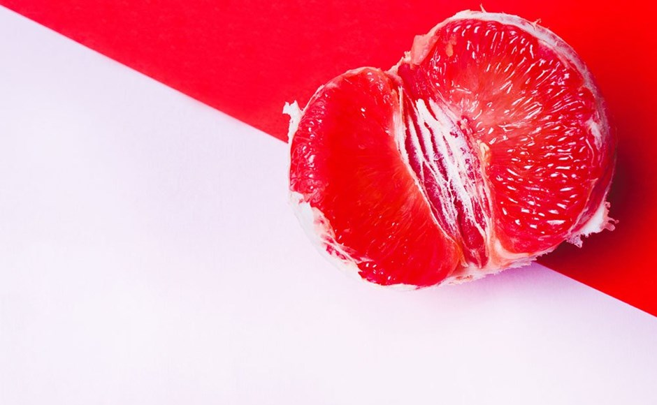 half a grapefruit on a pink and red background