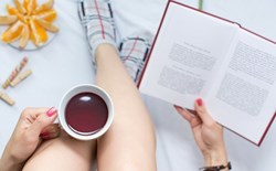 Woman drinking tea and reading