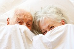Aging couple in bed being intimate