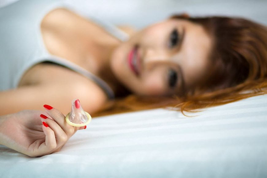 Woman holding a condom in bed