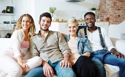 four people sitting closely on a couch