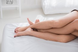 women with legs intertwined in bed