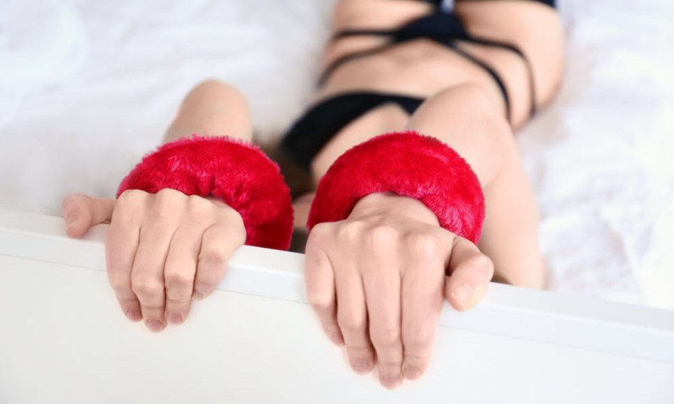 woman bound to bed with fluffy red handcuffs