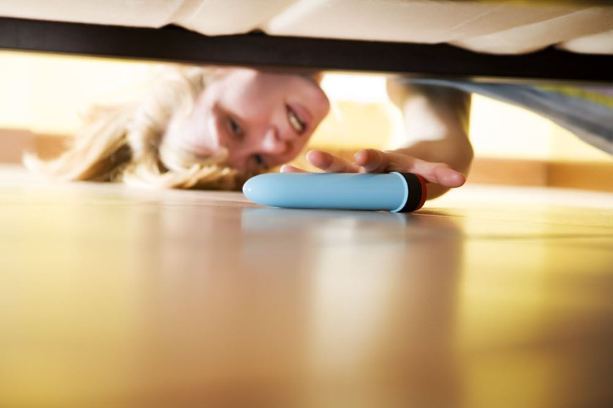 Woman reaching under the bed for her vibrator