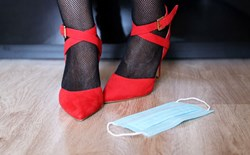 Sex toy boom and the pandemic, a discarded mask lies beside a pair of legs in fishnets and red high heels