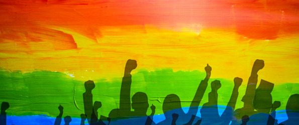 Rainbow Capitalism- the silhouettes of people with upraised fists against a rainbow painted wall