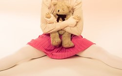 Childish woman holding teddy bear