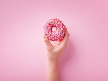 Woman hand holding pink donut on pastel background