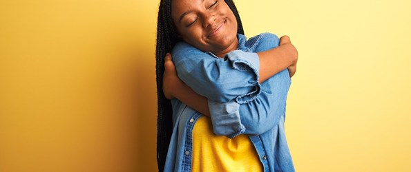 Young african american woman wearing denim shirt hugging herself