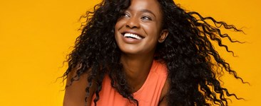 Young african woman laughing on yellow background